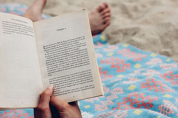 reading a book on the beach
