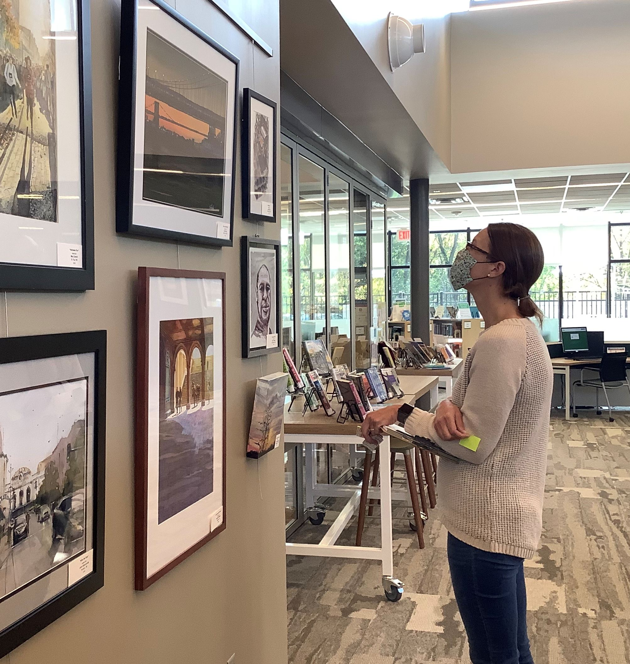 Juror viewing watercolor paintings at Wildwood LIbrary.
